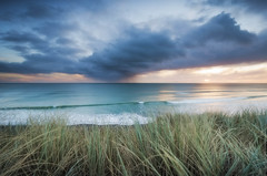 Passing Rain (Nick Twyford) Tags: sunset sea newzealand sky seascape colour nature grass rain clouds nikon waves wideangle nopeople auckland northisland westcoast portwaikato leefilters 1024mm d7000 lee06gndhard lee12gndsoft