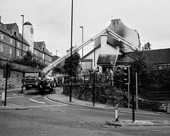 Firefighters Putting Out A Fire - Newcastle (Richard James Palmer) Tags: mamiya7ii mamiya 7ii 80mm ilford hp5 ilfordmicrophen microphen ishootfilm shoot film iso 400 iso400 ilfordhp5 f4 newcastle northeast north east street photography streetphotography portrait black white rangefinder medium format 120 filmisnotdead analogue documentary epsonperfectionv700 epson v700 1125 newcastleupontyne upon tyne tyneandwear northern uk england urban melancholy art fineart new overcast isolated walkabout 2016 gritty gloomy abstract trapped blackandwhite monochrome firefighters fire