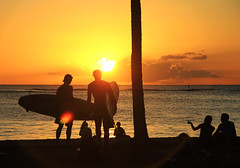 Day's End in the Aloha State (` Toshio ') Tags: ocean blue sunset sun men water silhouette yellow clouds hawaii women surf waves pacific silhouettes surfing lensflare surfboard flare surfers honolulu waikikibeach toshio
