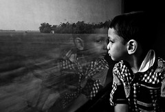 Untitled (swarat_ghosh) Tags: portrait blackandwhite india reflection window glass monochrome face train asian nikon indian posture insidetrain kidsportrait d3000 yahoo:yourpictures=yourbestphotoof2012