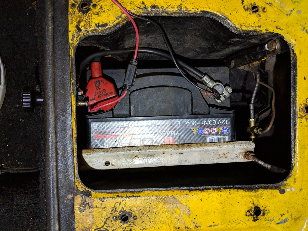 Top-down view of the battery box with the battery in place, showing the earth and live cables laid around the side of the battery to the switch