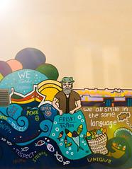 We all smile in the same language (lorenzoviolone) Tags: d5200 dslr fisherman fujiastia100f mural nikon nikond5200 reflex vsco vscofilm beauty flare flares muralart paint painted painting phrases streetphoto streetphotocolor streetphotography travel:malta=aug2016 marsaxlokk malta fav10