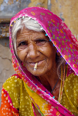 Little Old Lady (Jo Pye) Tags: old travel pink light summer portrait people orange woman india color colour travelling face yellow lady outside lumix person eyes colorful asia pattern humanity expression cigarette indian smoke smoking panasonic traveller story backpacking elderly