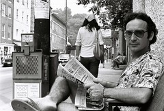 A casual photographer reading the local paper and relaxing in front of his apartment at 8069 Main Street, Ellicott City, summer 1977.  Photo taken by a friend with the photographer's camera. (A CASUAL PHOTGRAPHER) Tags: portraits men johnlbeck photographers ellicottcity maryland howardcounty minoltasrt101 kodakplusxfilm analogphotography clothingdress hawaiianshirts newspapers mainstreet