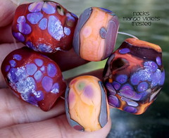 Rocks Mango Violets Frosted (Laura Blanck Openstudio) Tags: openstudio openstudiobeads glass handmade lampwork beads bead set jewerly murano big fine arts artist artisan show festival wearable pebbles stones rocks nuggets faceted transparent whimsical funky odd colorful multicolor organic earthy abstract asymmetric frit speckles made usa published winner category south miami mango coral orange maize copper green rubino maroon ruby violet grape lavender lilac purple eggplant plum mauve matte etched frosted opaque glow