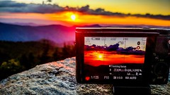 taking sunset photo with a camera in the mountains (DigiDreamGrafix.com) Tags: taking sunset photo witha camera inthemountains mount mitchell nc northcarolina nature red fiery hills horizon evening beautiful breathtaking making creative pointandshoot sun setting autumn summer season glare screen buttons click shutter body dslr slr film digital technology burnsville unitedstates