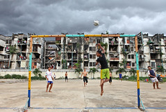 A socialist  housing project, Phnom Penh, Cambodia (www.igorbilicphotography.com) Tags: city urban white playing storm game building sport horizontal clouds ball children football goal community asia cambodia call mood cambodians play center barefoot phnompenh ghetto slum khmerrouge patang kampuchea capitalcities nogomet thewhitebuilding igorbilic humansettlement