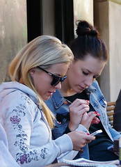 Hold my hand (Jumpin'Jack) Tags: street girls red two flower caf sunglasses mobile holding hands women pretty pattern phone looking bright telephone nail fingers young cellular polish jeans jacket blonde while brunette iphone atthe