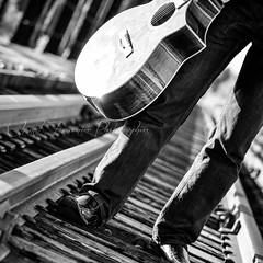 My Guitar ... My World (Chantal Fournier (Bayan Paparazzi)) Tags: road wood travel bridge blackandwhite bw musician music sun man reflection sunshine metal horizontal walking square blackwhite track day angle guitar walk ottawa horizon perspective rail jeans coveredbridge strings traveling guitarist sunreflection sunnyday accoustic traveler rayoflight railtrack manwalking vetical abandonedbridge blackwhitephotos mygearandme rememberthatmomentlevel1 bayanpaparazzi rememberthatmomentlevel2 chantalfournier