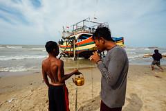 Lighting Cigarette Near Fishing Boat, Indonesia (AdamCohn) Tags: adamcohn indonesia tuban tubanregency boat fishing fishingboat kapal kapalnelayan ship shipsboats wwwadamcohncom bancar