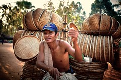 Cambodia - Siem Reap - The carrier of baskets (Roberto Farina Travel Photography) Tags: portrait travelling canon asia cambodia streetphotography streetportrait siemreap carry reportage travelphotography cambogia indocine reportagediviaggio orangehour viaggioincambogia