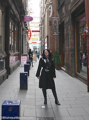 Glasgow Mackintosh City - 4/6 (Mistress Maggie dot com) Tags: plastic coat pvc mackintosh belted mac shiny black boots waterproof rainwear raincoat standing outdoors public lighthouse glasgow fetish mature leather booted kneeboots lady woman female mistressmaggie mistress domme dominatrix