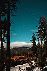 Caribou Gleam (Amanda.T) Tags: longexposure trees light sky house snow mountains night clouds stars lights astrophotography amandatonis