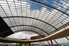 Bus turn around (Johan Konz) Tags: busstation turnaround roof road red bus blue sky white clouds architecture openspace outdoor ijriver centralstation amsterdam netherlands building ceiling buildingstructure structure steelstructure curve infrastructure public transportation publictransportation panes glass nikon d90