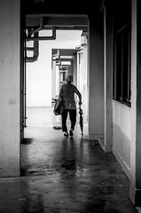 A Lonely Passage (YuJin Lim) Tags: street bw umbrella bag singapore pipes corridor oldlady