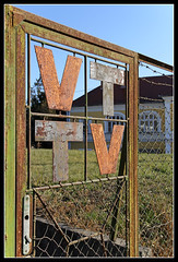 Tab - rusty, old Videoton sign (Romeodesign) Tags: door old colors sign metal logo grid tv gate closed paint hungary rusty rail used tor keyhole vt tab gitter 550d somogy videoton