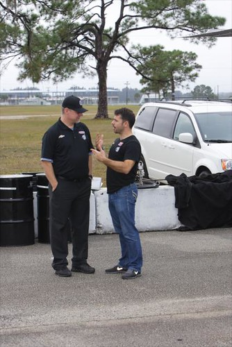 Oriol Servia, right, talks with a member of his Panther/Dreyer & Reinbold Racing crew while waiting for the track to dry