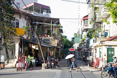 Urban Jungle ([Alexandre]) Tags: streetphotography backacking railway urban city asia tracks street house umbrella walking traval canon vietnam explore hanoi hànội vn