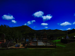 Sombre Places (Steve Taylor (Photography)) Tags: art digital landscape fence church railing blue green brown white newzealand nz southisland canterbury bankspeninsula grass tree cloud sky cemetery graveyard grave hills hill littleriver saint st andrews anglican view