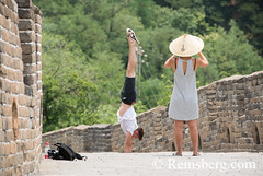 Mutianyu, China - Woman wearing an Asian conical hat taking pictures of a man doing a handstand on the Great Wall of China. The wall stretches over 6,000 mountainous kilometers east to west across North China and through 15 provinces. (Remsberg Photos) Tags: asia china mutianyu eastasia beijing greatwall world greatwallofchina wonderoftheworld mountains architecture photography travel destination nature internationallandmark brick builtstructure ancient history protection culture fortifiedstructure province landscape beauty tourists woman asianconicalhat bamboohat man handstand chn