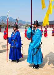 SEOUL - MARCH 30: Royal guards during the changing of the guard ceremony at Gyeongbokgung Palace, March 30, 2011, Seoul, South Korea (Maxim Tupikov) Tags: travel red portrait people man building male art history tourism architecture asian religious army ancient uniform asia meditate arch tour expression flag military south traditional faith religion north guard ceremony culture royal belief buddhism landmark palace korea historic korean national weapon seoul sword meditation tradition meaning pavillion cultural gyeongbokgung protect