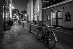 Bike Lane (McQuaide Photography) Tags: haarlem noordholland northholland netherlands nederland holland dutch europe sony a7rii ilce7rm2 alpha mirrorless 1635mm sonyzeiss zeiss variotessar fullframe mcquaidephotography adobe photoshop lightroom tripod manfrotto light licht lowlight night nacht nightphotography architecture outdoor outside gebouw building wideangle wideanglelens groothoek blackandwhite bw blackwhite mono monochrome city stad house huis huizen residential old oud oldhouse oldbuildings longexposure street straat bike fiets bicycle transport transportation urban