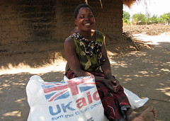 Saukila, a farmer in southern Malawi, smiles as she collects a sack of maize at a WFP food distribution point (DFID - UK Department for International Development) Tag