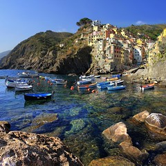The coast of Riomaggiore plunges steeply into the sea (Bn) Tags: world ocean park flowers blue trees houses sea summer vacation sky orange sun sunlight holiday flower tower heritage classic water colors beautiful weather train buildings walking coast boat high warm mediterranean italia day sailing ship torre gulf view hiking path five liguria shoreline hike case cliffs lovers quay historic unesco via clear national wharf terre sail botanic mountainside quaint incredible viewpoint picturesque coloured cinque adriatic riomaggiore italianriviera torri yellew dellamore guardiolas