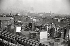 Mayor Frank Hague's Kingdom. Smokey, hazy, industrial  life at Jersey Avenue and 10th Street. Trains roll down the Erie Railroad's 10th street embankment.  The towers of Lower Manhattan hover remotely in the background. Jersey City. 1939 (wavz13) Tags: blackandwhite industry industrial dreary smokestacks bleak desolate oldnewyork dystopia dystopian urbanblight hudsoncounty oldfactory urbanwasteland oldtrains oldindustry industrialage industrialhistory industrialpollution oldfactories oldrailroad vintagenewyork bleakwasteland vintagetrains vintagefactory oldrailroads oldjerseycity vintageindustry jerseycityhistory newjerseyhistory 1930snewyork vintagejerseycity vintagenewjersey vintagefactories oldnewjersey 1930sjerseycity antiquerailroads vintagehudsoncounty 1930shudsoncounty antiquenewjersey antiqueindustry hudsoncountyhistory