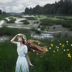 She Brings The Flowers (Rob Woodcox) Tags: surreal whimsical whitedress conceptual flowers floating hair longhair redhead redhair robwoodcox robwoodcoxphotography beauty model girl grass nature reeds river sky meadow field canada pei landandsee moody energy movement growth