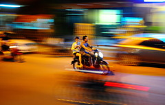,, Pokemon Go Hunters ,, (Jon in Thailand) Tags: panning laos lpdr asia street streetphotography streetpanning brokenribs nikon d300 nikkor 175528 people scooter colors pokemongo female red blue teal purple yellow green pokemongohunters