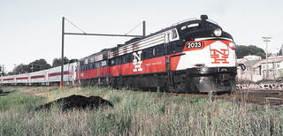 Metro-North Commuter Railroad EMD FL9 locomotive # 2023, is painted for the New Haven Railroad and is paired with MNCR EMD FL9 locomotive # 2028, and is seen while hauling a modern commuter train at an unknown location, 1980's, Mac Seabree Collection