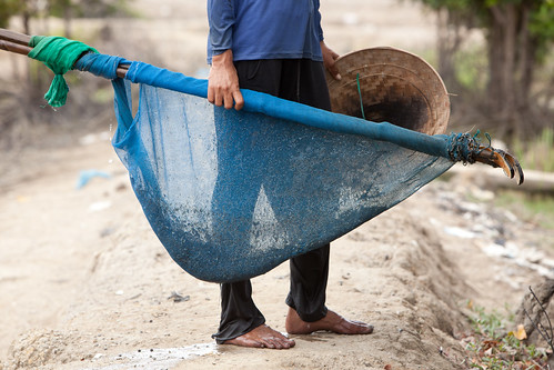 A shrimp farmer with his net after a catch. Photo by Mike Lusmore/Duckrabbit, 2012.