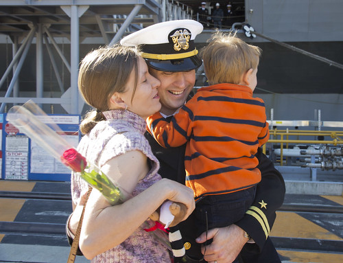 An officer hugs his children after returning home.