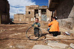 hanging on to what is left~ Kashgar (~mimo~) Tags: china mimokhairphotography xinjiang kashgar child family destruction wheel tire shadow sun documentary streetphotography portrait uyghur ethnicminority