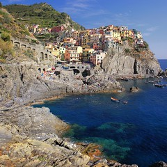 The beautiful little cliff side town Manarola drenched in vibrant colors (Bn) Tags: world ocean park pink flowers blue trees houses sea vacation sky orange sunlight flower tower heritage church water colors beautiful weather saint swimming buildings polaroid coast warm mediterranean italia sailing ship torre gulf hole hiking path five character liguria shoreline hike case cliffs quay historic bougainvillea unesco via vineyards national wharf terre sail ravine mountainside overlooking quaint inspire incredible viewpoint picturesque coloured topf100 manarola cinque giovanni italians italianriviera torri confraternita battista dellamore 100faves visipix guardiolas