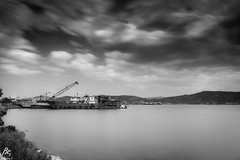 Where Dead Ships Dwell (sideris_bill) Tags: longexposure le sony a77ii blacknwhite black white bw nd nd1000 industrial landscape water ship shipwreck ships cloud clouds cloudporn sea seascape seaporn elefsina greece monochrome