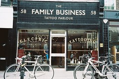 Walking in Clerkenwell - bikes in Exmouth Market and Tattoo Parlour (fabiolug) Tags: street people urban signs color colour reflection london film window colors bike bicycle sign electric shop tattoo reflections colours kodak wheels streetphotography bikes rangefinder tattoos number numbers cycle shops shopwindow portra clerkenwell farringdon shopfront cityoflondon 58 tattooing exmouthmarket olympus35rc londonist filmphotography tattooparlour portra160 kodakportra kodakportra160 ammaco thefamilybusiness believeinfilm walkinginclerkenwell