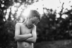 Angelic Upstart (markfly1) Tags: boy told off by mum looks down but really happy black white monochromatic shallow focus angelic sunlight simple pose hands crossed nikon d750
