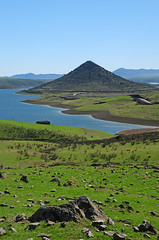 Autumn (Eve Livesey) Tags: road blue sky mountain lake green abandoned water grass farmhouse landscape spain rocks aqua shoreline windy reservoir volcanic bushes embalse conical extremadura embalsedelaserena