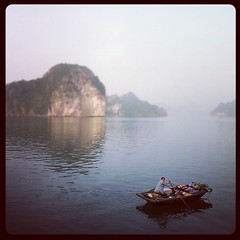 Early morning shopping in Halong Bay (Lil [Kristen Elsby]) Tags: ocean morning sea mist topf25 water square island bay boat vietnam squareformat editorial hudson topv4444 karst halong halongbay sampan iphone karsttower floatingshop iphoneography instagram instagramapp karstisland