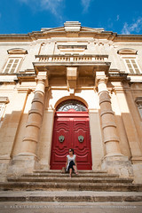Mdina (Alex Treadway) Tags: 3034years archaeology balcony baroque buildingentrance diminishingperspective facade female holiday malteseislands mdina medieval mediterraneanculture oldtown street thepast woman architecture buildingexterior builtstructure city clearsky day door doorknocker doorway elegant elevation entrance europe european front frontentrance frontage history holidaydestinations impressive island locallandmark lookingsideways malta old oldfashioned oneperson onepersononly outdoors people person pillars placeofinterest reddoor relaxed relaxing rising sandstone sitting steps stone town traditionalculture traveldestinations vacation vacationdestination vacations vertical walledtown windows