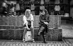 Smoke Break (Anne Worner) Tags: street blackandwhite bw blur lensbaby hair mono clothing women sitting boots bend bokeh candid longhair streetphotography smoking purse blonde conversation shopwindow resting bergen brunette talking leatherjacket crossedlegs shoppingbag bendy displaywindow selectivefocus manualfocuslens sweet35 anneworner