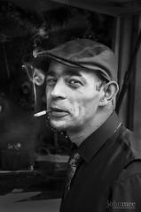 Smoking man (John Mee Photography) Tags: hello street ireland urban man galway photography market cigarette smoke stall macaroon cap marketplace smoker fag seller trader