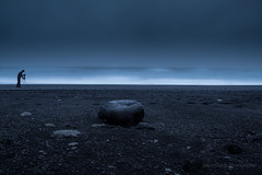 a man, a rock and the sea (Explored) (JorunnSjofn) Tags: ocean blue winter sea beach rain rock iceland photographer stones january roadtrip le southshore reynisfjara reynisdrangar 18135 2013