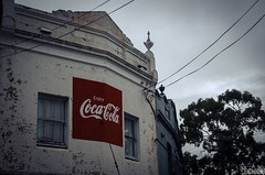 Coca-Cola (smellerbee) Tags: australia sydney newtown enmore hipster digital colour color pentax pentaxkr blue coke cocacola sign words writing lines sky trees windows shop buiding old paint