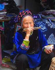 Enjoy you meal (Py All) Tags: blue portrait woman face lady lunch costume asia eating femme traditional bleu eat baguette manger chopstick  tradition yunnan dali rue chine visage vieille od  tenue  traditionnel