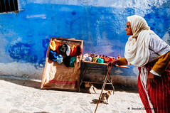 Chefchaouen. Morocco (achel cabonell) Tags: africa street city travel blue people urban woman motion animal wall cat walking souvenirs headscarf hijab stall viajes morocco maroc elder medina chaouen chefchaouen marruecos onthemove moroccan winterhat brightcolours travelphotography traditionalclothing documentaryphotography xauen buildingexterior fotografiadocumental fotografiadeviajes rachelcarbonell