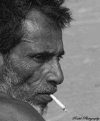 Forgetting Smoke. (Bird Graphy) Tags: life old portrait bw man black broken monochrome america project photography rebel photo alone time russia smoke national always dhaka behind geography dslr past discovery bd bangladesh dsc t3i day350 drakness rakib togetherforsway birdgraphy
