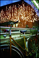 Lights And Bike (Boris Brckhuser) Tags: street city blue light urban orange color film bike night 35mm evening globe lowlight colorful glow dof bokeh dusk pavement grain handheld bb hue available bleue fragments lheure autaut frameborder